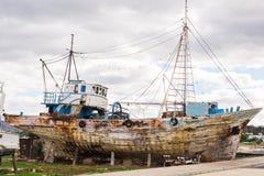 De verlaten gebroken schipbreuk beached op rotsachtige overzeese kust royalty-vrije stock afbeelding