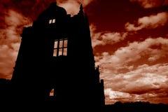 De verlaten geruïneerde bouw met een rode hemel Royalty-vrije Stock Foto's