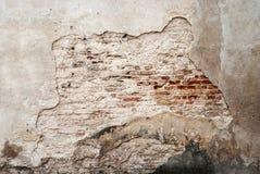 De verlaten grunge gebarsten muur van de baksteengipspleister Stock Foto's