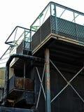 De verlaten verlaten industriële bouw met de de roestende tanks en pijpen van staalbalken royalty-vrije stock afbeeldingen
