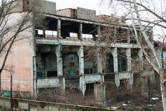 De verlaten industriële bouw openlucht met vegetatie en graffiti stock afbeelding