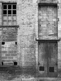 De verlaten industriële pakhuisbouw met bricked omhoog vensters stock afbeelding
