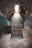 De verlaten ruimte van de gevangeniscel met oude roestige van de bedkader en schil muren Royalty-vrije Stock Foto's