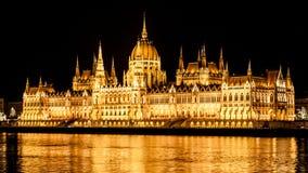 De verlichte historische bouw van het Hongaarse Parlement op de Rivierdijk van Donau in 's nachts Boedapest Stock Afbeeldingen