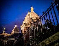 De verlichte koepels van Sacre Coeur, Parijs, tegen een diepe blauwe nachthemel Royalty-vrije Stock Foto