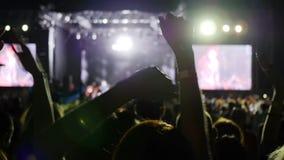 De verlichte scène door kleurrijke verlichting tijdens het festival van de nachtrots, vele lichten op stadium, mensen slaat wapen stock video