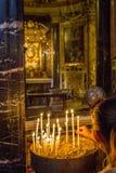 De verlichtingskaarsen van de vrouwenhand in een kerk stock afbeelding