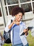 De Verliezersteken van studentenholding books while Gesturing Stock Afbeelding