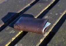 De verloren portefeuille met contant geld op een parkbank Stock Afbeeldingen
