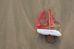 De verloren stuk speelgoed boot waste hierboven omhoog op strand van stock afbeeldingen