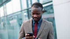 De vermoeide Afrikaanse Amerikaanse zakenman leest iets in zijn smartphone die zich buiten bevinden Mens die sms gebruikend app t stock video