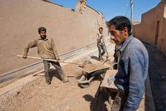 De vermoeide arbeiders leggen weg in de smalle straten van oude stad Royalty-vrije Stock Foto's