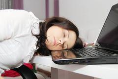 De vermoeide bedrijfsvrouw viel in slaap naast laptop Stock Afbeelding