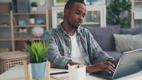 De vermoeide, beklemtoonde en slaperige freelance arbeiders Afrikaanse Amerikaanse kerel gebruikt laptop thuis en geeuw het voele stock footage