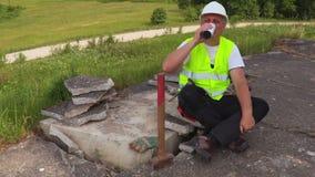 De vermoeide bouwvakker drinkt koffie stock videobeelden