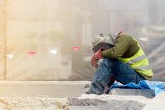 De vermoeide bouwvakker in het groene vest en de rode handschoenzitting in het bouwgebied stock afbeeldingen