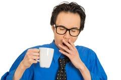 De vermoeide dalende in slaap jonge kop van de zakenmanholding van koffie stock foto