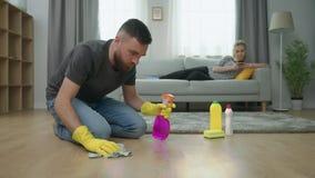 De vermoeide echtgenoot maakt parketvloer schoon, en zijn vrouw ligt op bank met smartphone stock videobeelden
