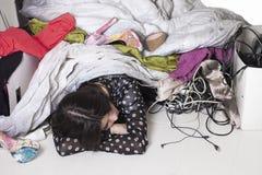 De vermoeide en beklemtoonde meisjesslaap knoeit onder stock foto
