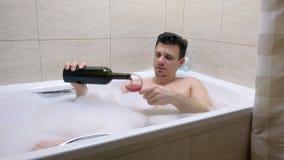De vermoeide gedronken mens ligt in bad, giet en drinkt wijn van een wijnglas stock videobeelden