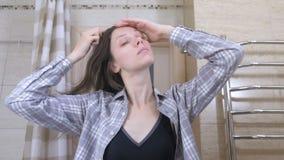 De vermoeide gewekte vrouw kamt haar haar die zich voor een spiegel in de badkamers bevinden stock videobeelden