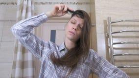 De vermoeide gewekte vrouw kamt haar haar die zich voor een spiegel in de badkamers bevinden stock video