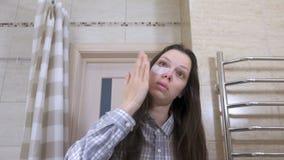 De vermoeide gewekte vrouw met een kater zet flarden op de ogen in de badkamers stock footage