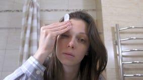 De vermoeide gewekte vrouw verwijdert flarden uit de ogen in de badkamers stock videobeelden