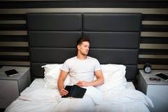 De vermoeide jonge mensenslaap in slaapkamer in zitting stelt Hij houdt zwart boek op knieën De kerel is behandeld met witte deke royalty-vrije stock afbeeldingen