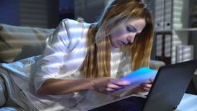 De vermoeide jonge onderneemster ontwaakt plotseling en feverishly werkend in het bureau met laptop stock videobeelden