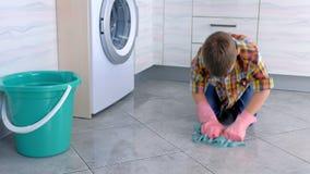 De vermoeide jongen in rubberhandschoenen wast de vloer in de keuken Het huisplichten van het kind stock footage