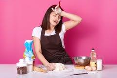 De vermoeide koktribunes met gesloten ogen bij lijst in keuken, houdt hand op voorhoofd, besteedt zich met het kneden van deeg Jo royalty-vrije stock foto