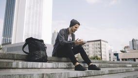De vermoeide maar gelukkige toerist zit op de stappen op de straat en houdt de plaat met de lunch royalty-vrije stock afbeelding