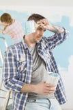 De vermoeide man holdingsverf kan en met vrouw het schilderen op achtergrond borstelen royalty-vrije stock foto