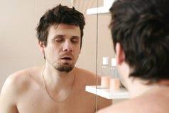 De vermoeide mens die net is ontwaakt bekijkt zijn gedachtengang in de spiegel en de slaap die zich nog bevinden royalty-vrije stock foto