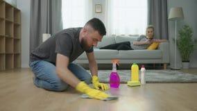 De vermoeide mens maakt parketvloer schoon, en de vrouw ligt op bank met smartphone stock video