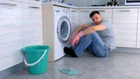 De vermoeide mens in rubberhandschoenen heeft een rust van het schoonmaken zitting op de keukenvloer stock videobeelden