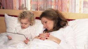 De vermoeide mooie in slaap daling van de moedervrouw terwijl dochter het letten op tabletcomputer stock footage