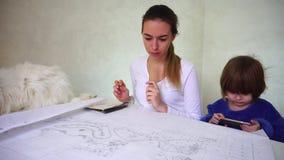 De vermoeide ontwerper leidt door dochter en huisdier af stock footage