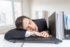De vermoeide overwerkte mens slaapt op toetsenbord in bureau op het werk stock foto