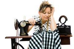 De vermoeide slaap van de vrouwennaaister door handmachine te naaien - overwerkte werkverslaafdedromen royalty-vrije stock foto