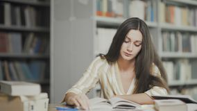 De vermoeide student treft voor onderzoek voorbereidingen bij universitaire bibliotheek stock video
