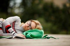 De vermoeide student viel in slaap voor handboeken in werf Stock Afbeelding