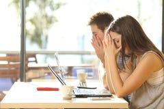 De vermoeide studenten die in een koffie bestuderen winkelen stock foto