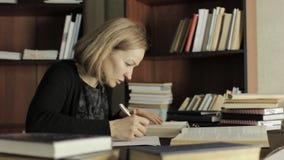 De vermoeide studentenvoorbereiding werkt natuurlijk in een bibliotheek in universiteit, die voor examens voorbereidingen treffen stock videobeelden
