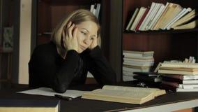De vermoeide studentenvoorbereiding werkt natuurlijk in een bibliotheek in universiteit, die voor examens voorbereidingen treffen stock footage