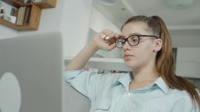 De vermoeide tienerstudent typt thuis op laptop, voorbereidingen treffend voor examens of thuiswerk stock video