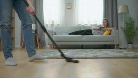 De vermoeide vloer van het echtgenoot zuigende parket, en zijn vrouwenspelen op smartphone op laag stock video