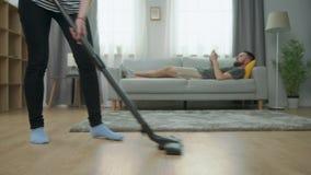 De vermoeide vloer van het vrouwen zuigende parket en haar echtgenootspel op smartphone op bank stock video