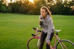 De vermoeide vrouw dooft dorst na het berijden van een fiets Stock Afbeeldingen